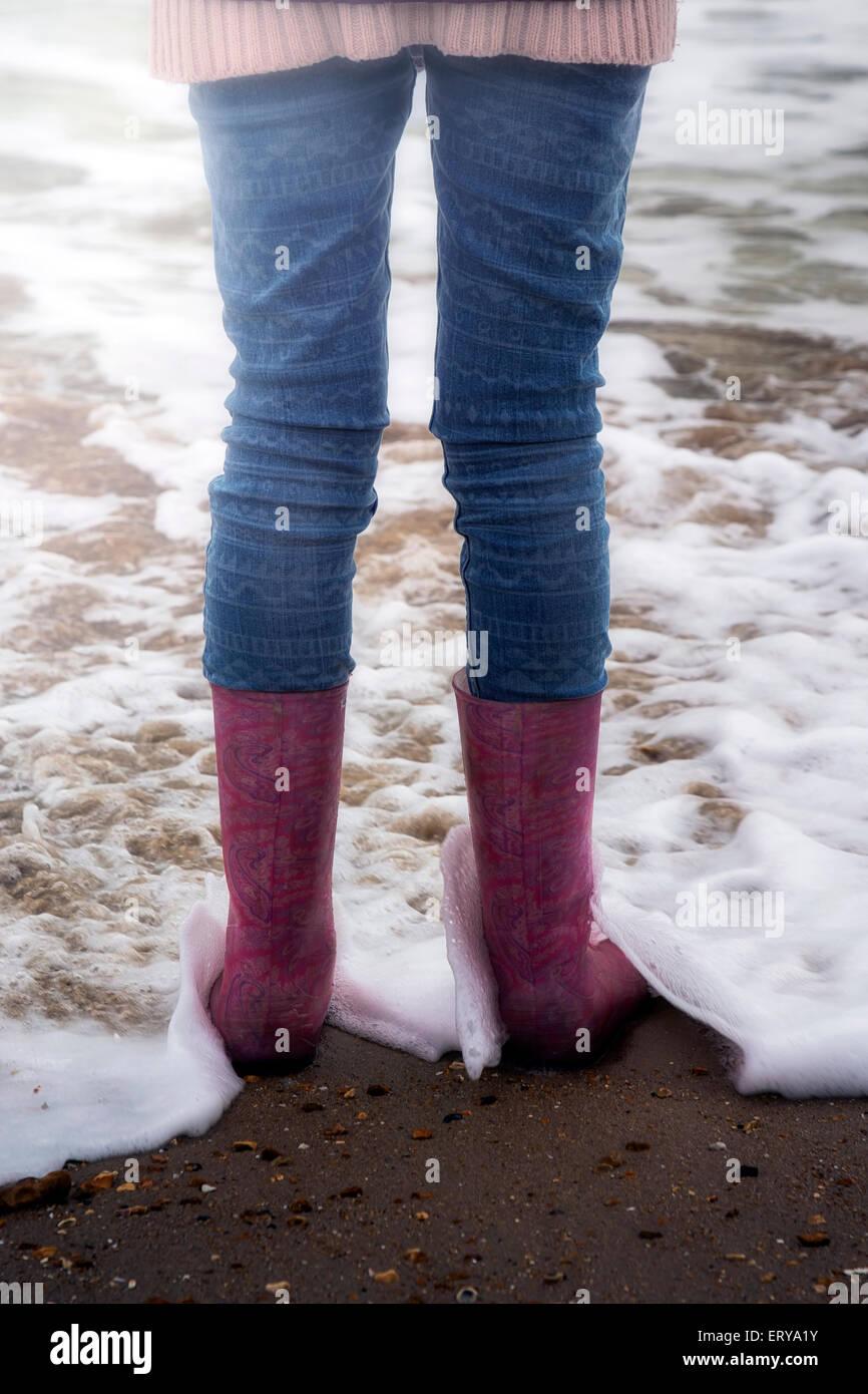 ein Mädchen steht mit Gummistiefeln am Strand Stockbild