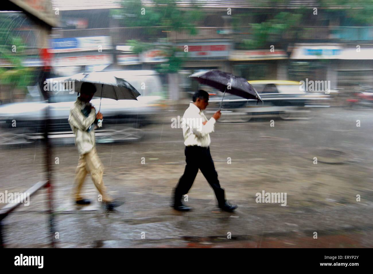 Pendler schützen sich mit ihren Regenschirmen, wie sie in heftige Regenfälle während der Monsunzeit Stockbild