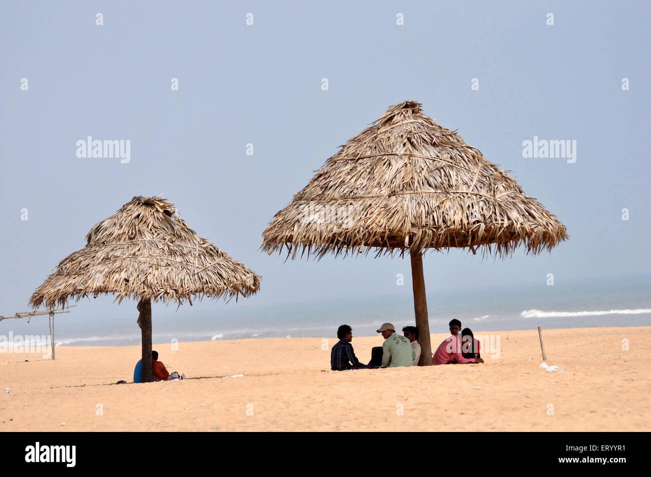 Touristen unter Sonnenschirmen am Strand; Puri; Orissa; Indien Stockfoto