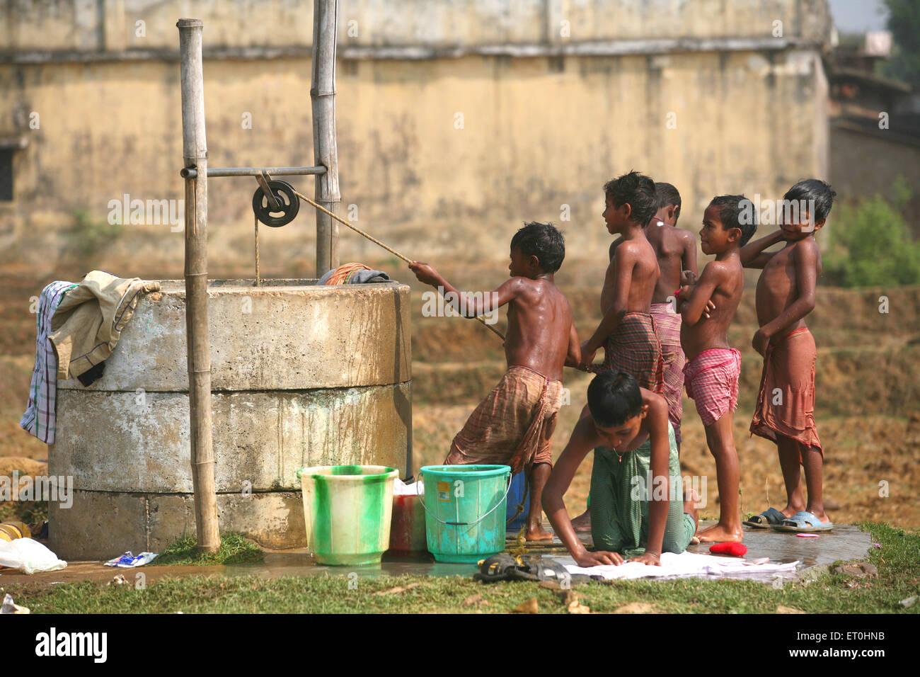 Kinder ziehen Wasser aus Brunnen, Bad Boy Wäsche am Brunnen in Jharkhand zu nehmen; Indien; KEIN HERR Stockbild