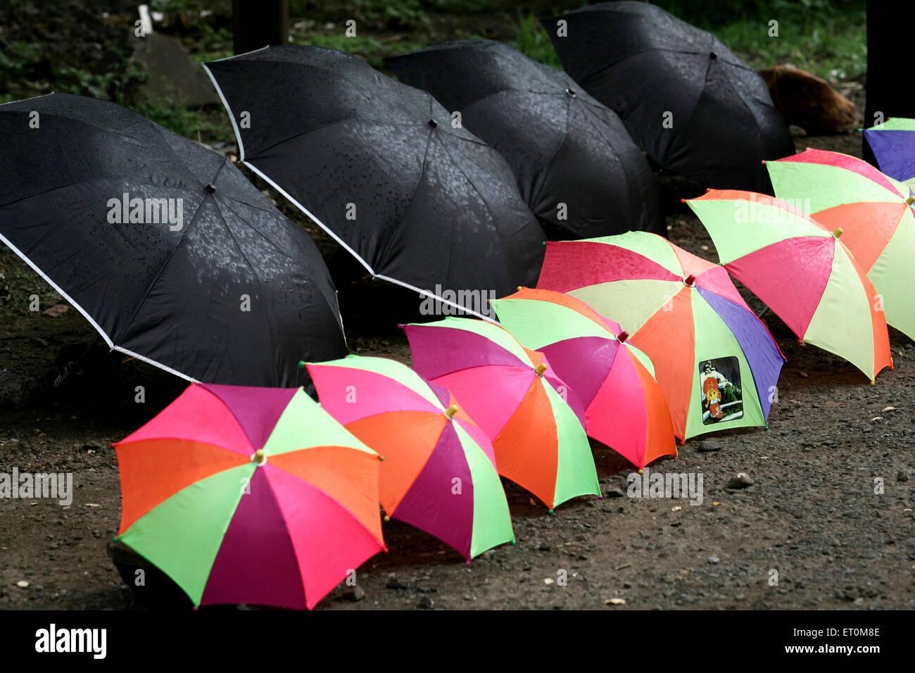 Bunte und schwarze Regenschirme für den Verkauf auf Autobahn Mumbai Pune gehalten; Maharashtra; Indien Stockbild