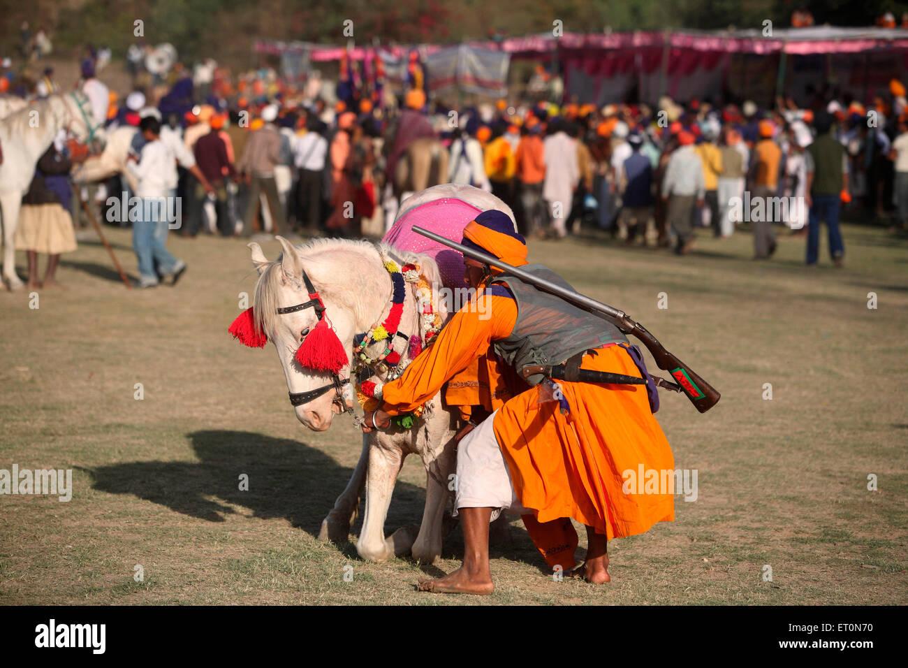 Nihang oder Sikh Krieger mit Gewehr und Pferd während der Hola Mohalla Feier bei Anandpur Sahib in Rupnagar Stockbild