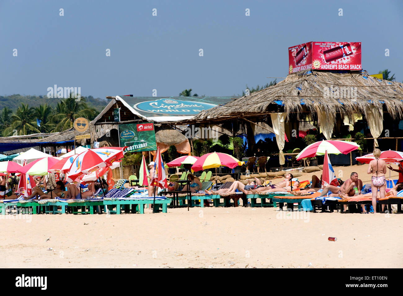 Große Sonnenschirme und Holzbetten in Calangute Beach; Goa; Indien Stockbild