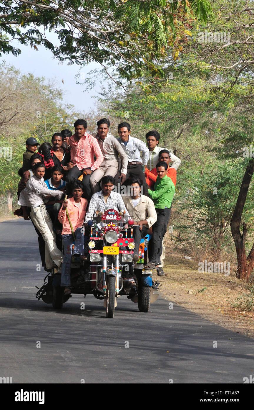 Siebzehn Männer auf rikscha taxi Dreirad auf Motorrad Chhota Udaipur Gujarat Indien Stockbild