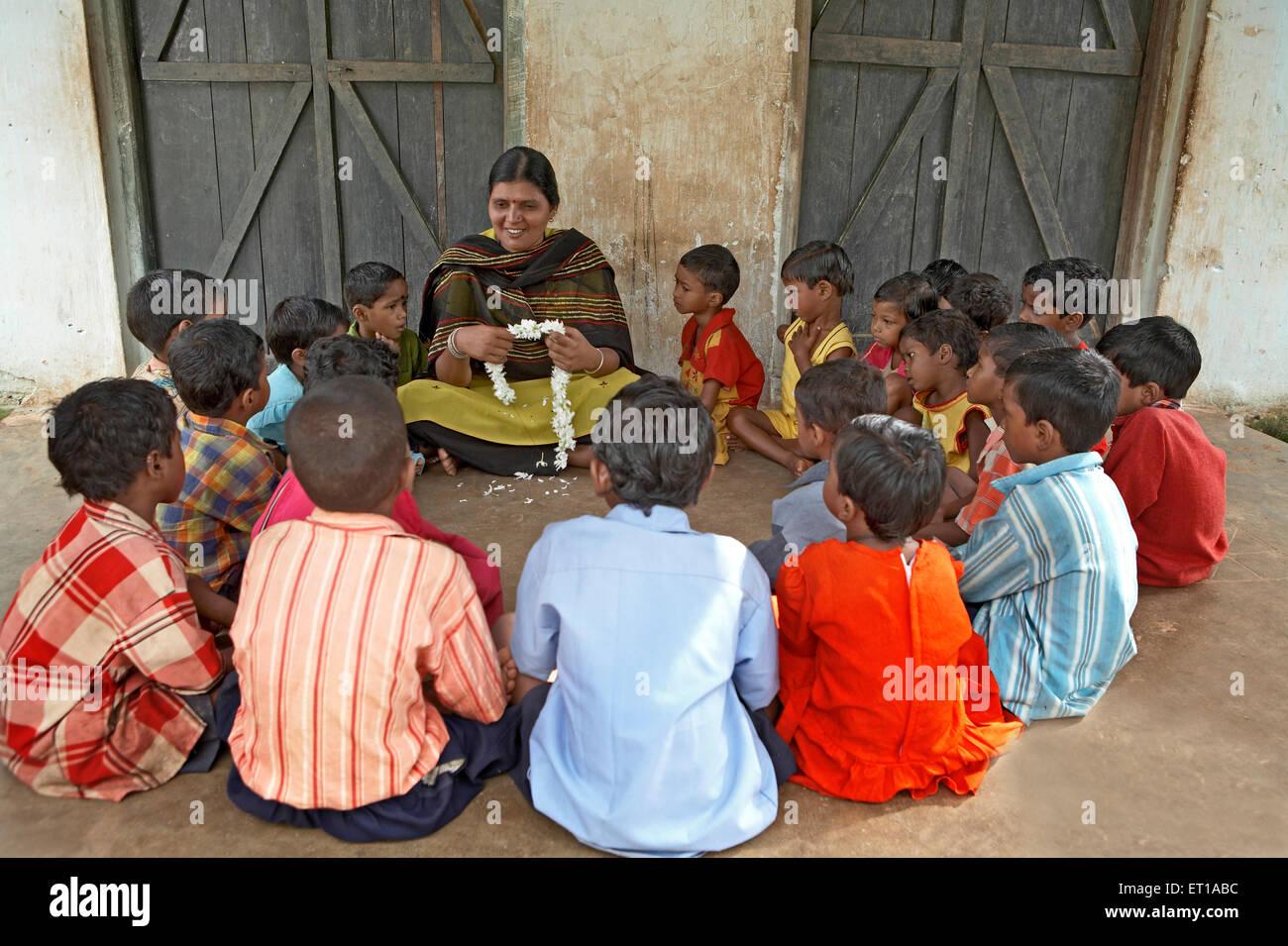 Lehrerin in der Dorfschule mit Kindern soziale Initiative begonnen von NGO Chinmaya Organisation der ländlichen Stockbild