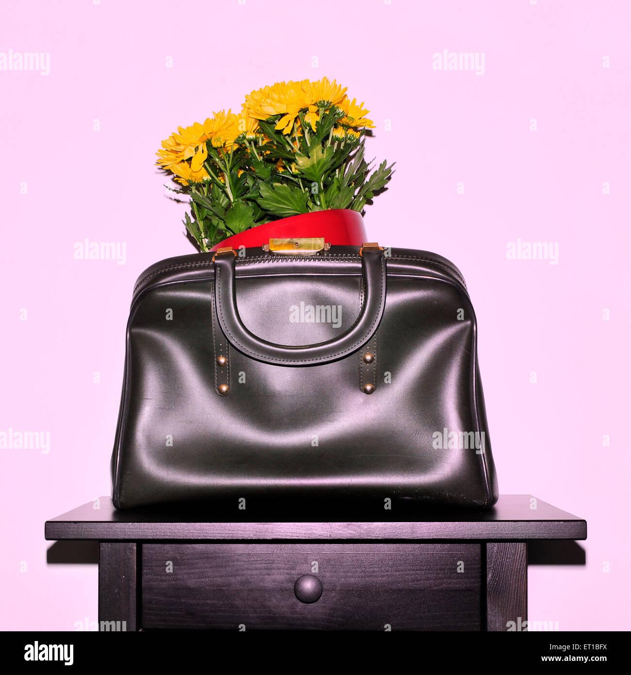 Gelbe Chrysanthemen in einer Vintage-Leder-Tasche auf einem schwarzen Tisch mit einem Retro-Snapshot-Effekt Stockbild