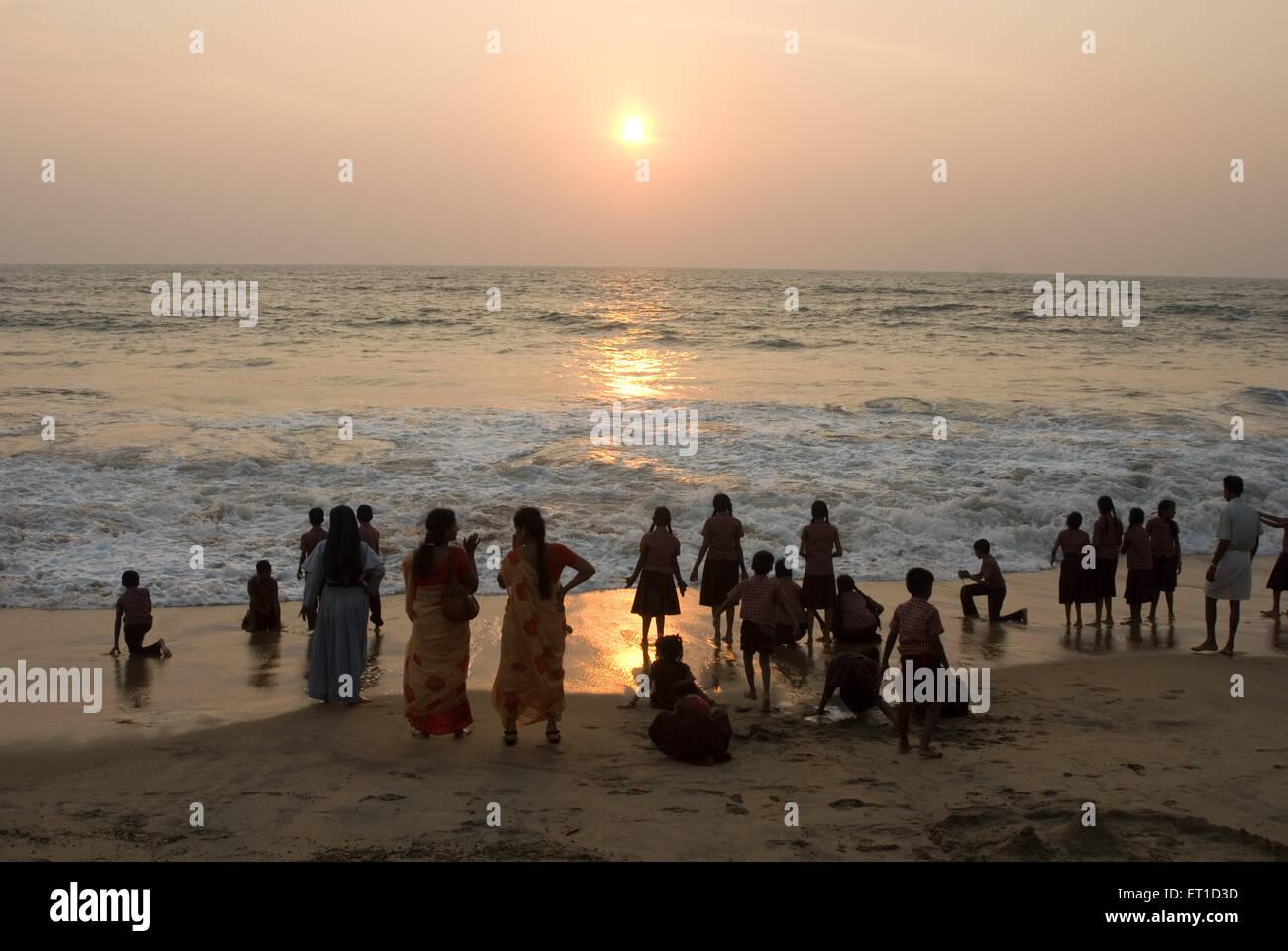 Schulkinder mit ihren Lehrern Sonnenuntergang am Strand von Cherai; Cochin; Kerala; Indien Stockbild