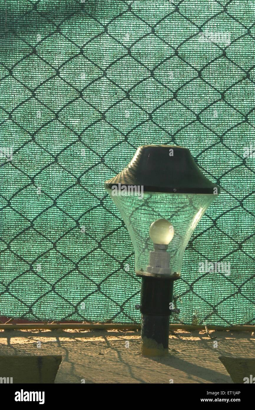 Lampenschirm gegen gekreuzten Mesh und grünen Tuch im Holiday Resort; Wai; Maharashtra; Indien-abstrakt Stockbild