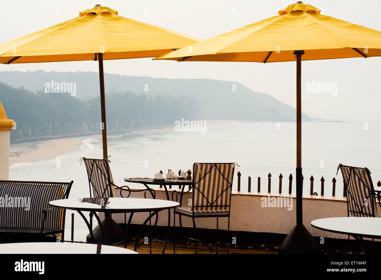 Gelbe Sonnenschirme und Meer im Hotel Terakhol Festungen; Goa; Indien Stockbild