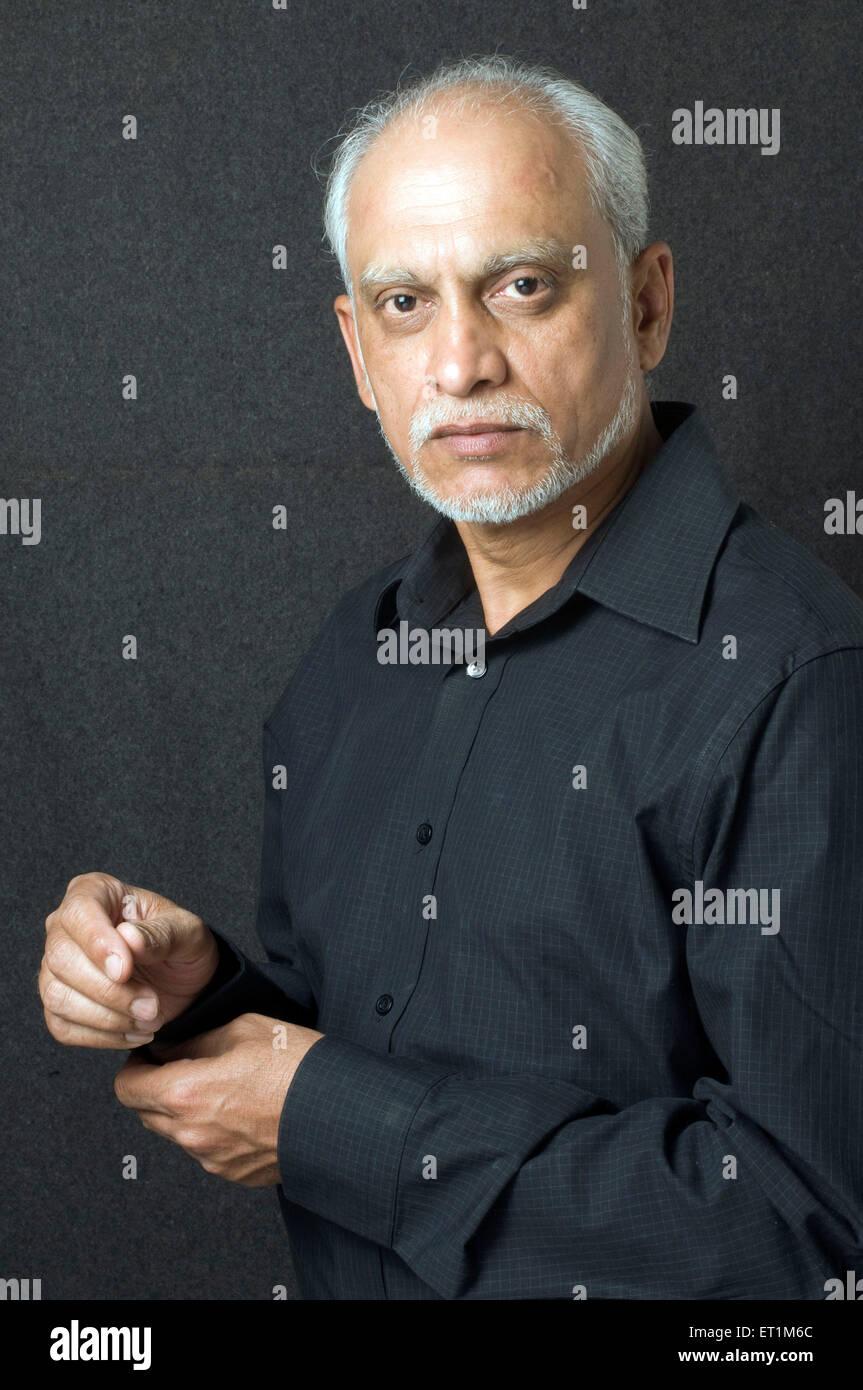 Alter Mann im schwarzen Hemd voll und knöpfte Manschetten - Model Release # 686 P Stockfoto