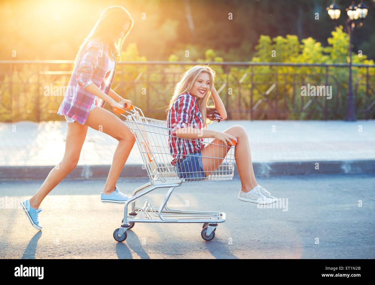 Zwei glückliche schöne Teenie Mädchen fahren Einkaufen Warenkorb im Freien, Lifestyle-Konzept Stockbild