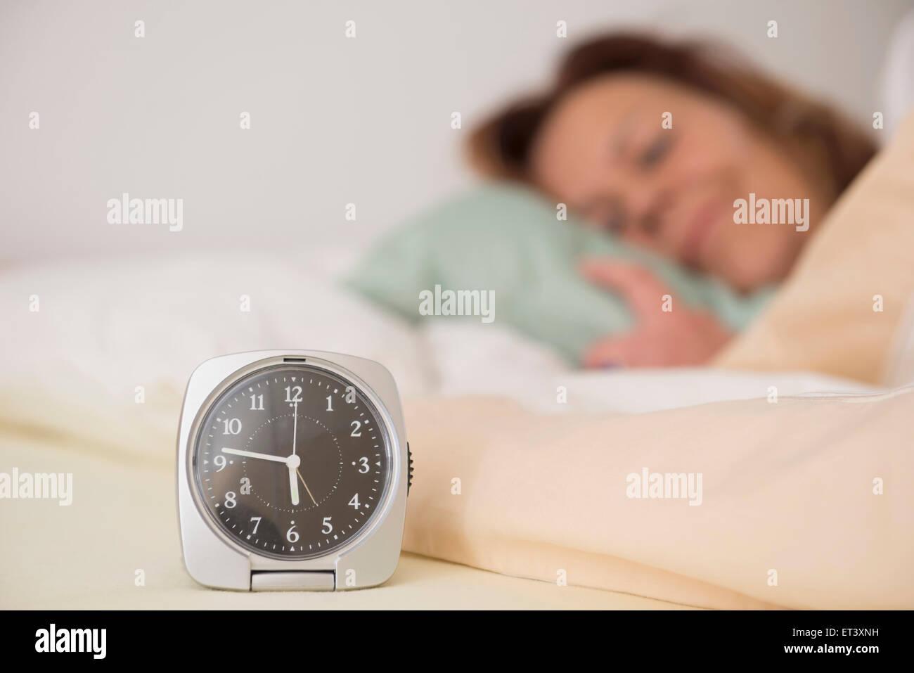 Frau schlafend im Bett während ihr Alarm die frühe Zeit zu Hause im ...
