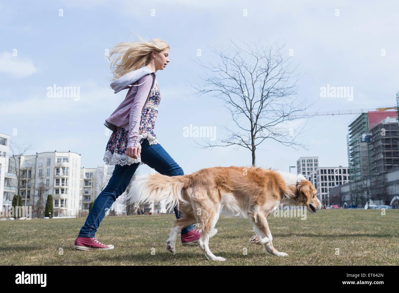 Seitenansicht des Mädchens zu Fuß im Park mit Hund, München, Bayern, Deutschland Stockbild