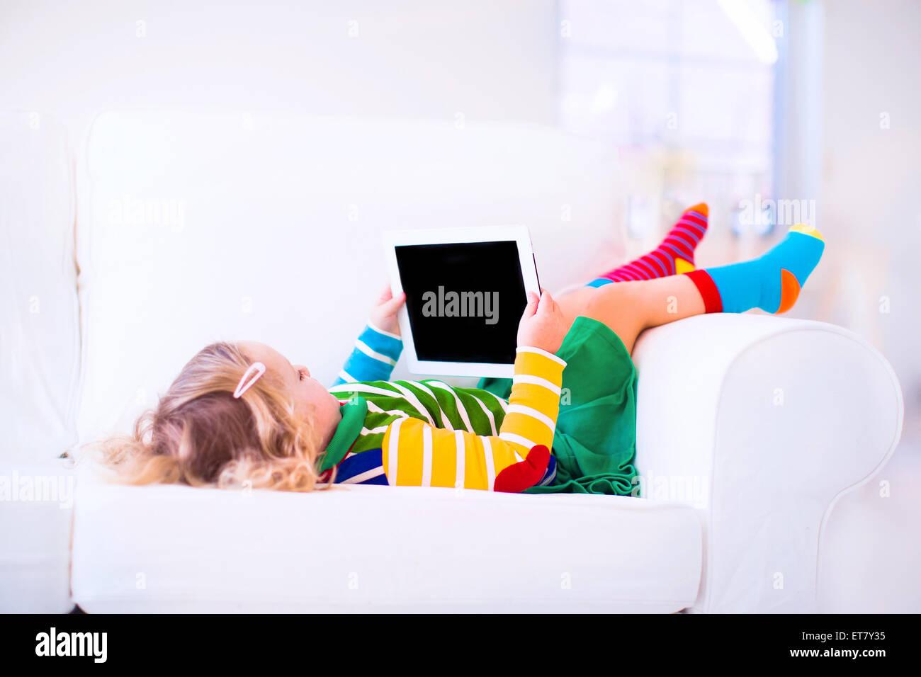 Lustige Kleine Kleinkind Madchen Mit Tablet Pc Auf Einem Weissen Sofa