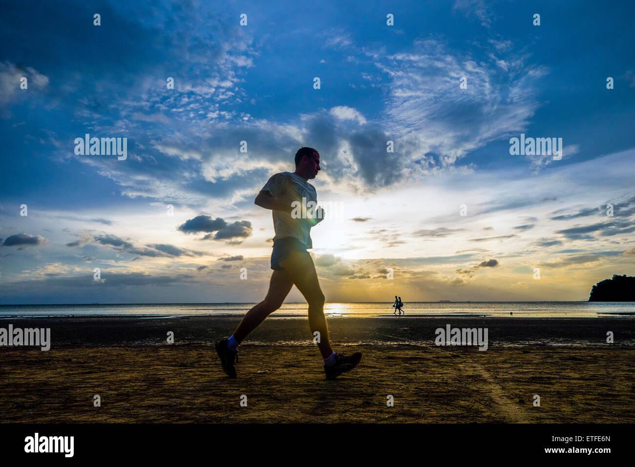 Asien. Thailand. Insel Koh Lanta. Jogger am Strand bei Sonnenuntergang. Stockbild