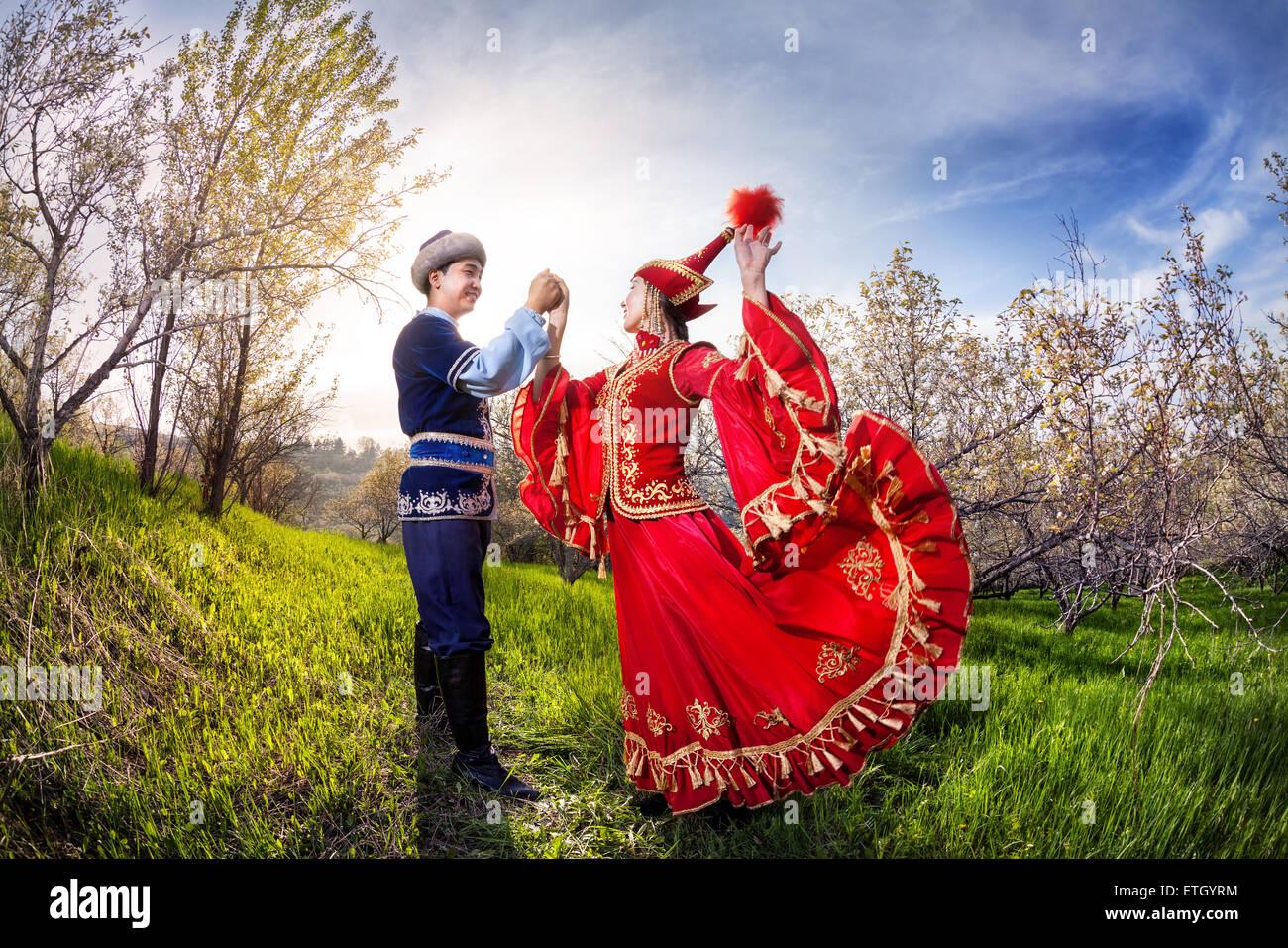 Kasachische Frau tanzt im roten Kleid mit Mann im Frühjahr Apfelgarten in Almaty, Kasachstan, Zentralasien Stockbild