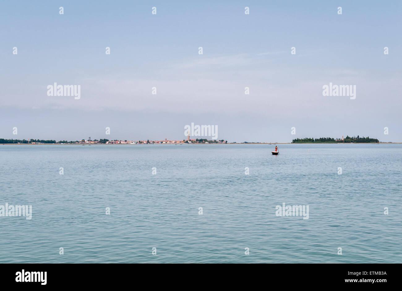 Venedig, Italien. Fernblick über die Stadt in der Lagune, ein einsamer Mann, der sein Boot über das seichte Stockbild