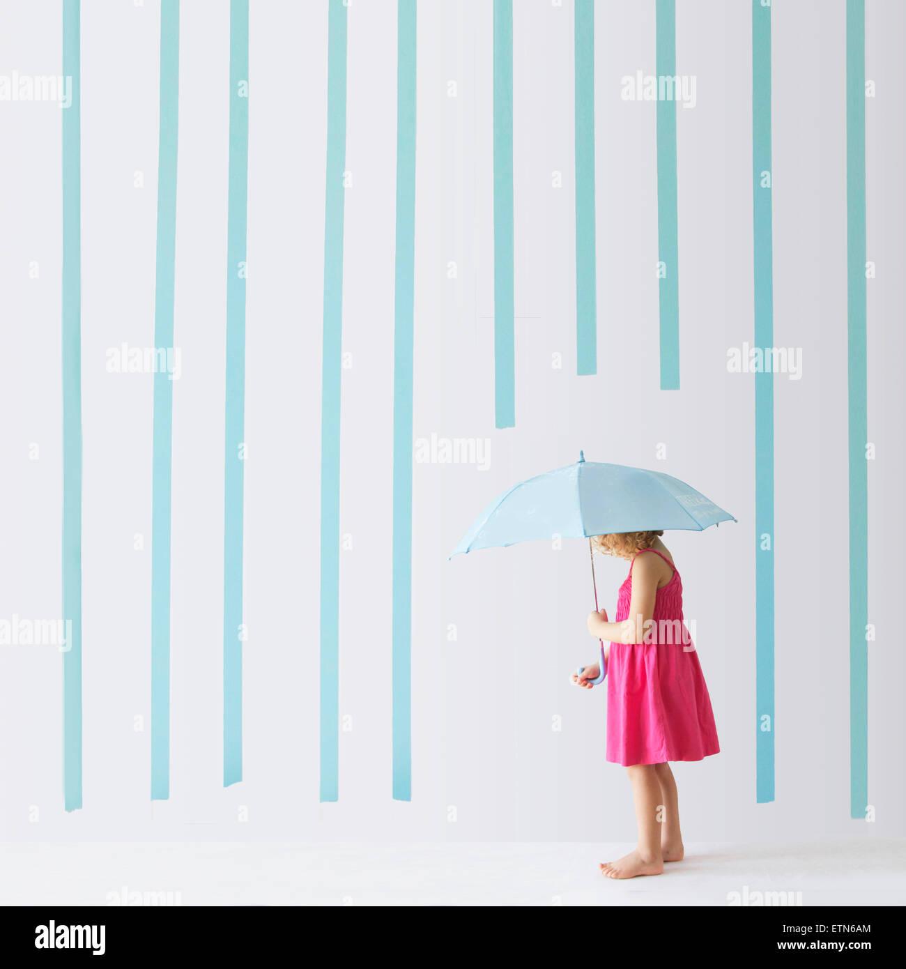 Mädchen mit einem Regenschirm stehen unter Regen machte der Streifen Stockbild