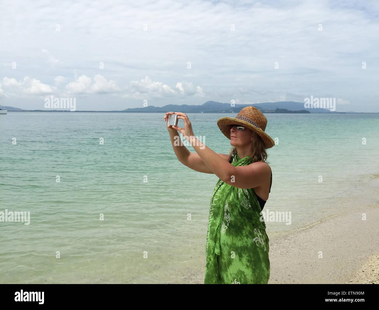 Frau am Strand mit einem mobilen Gerät ein Foto aufnehmen Stockbild