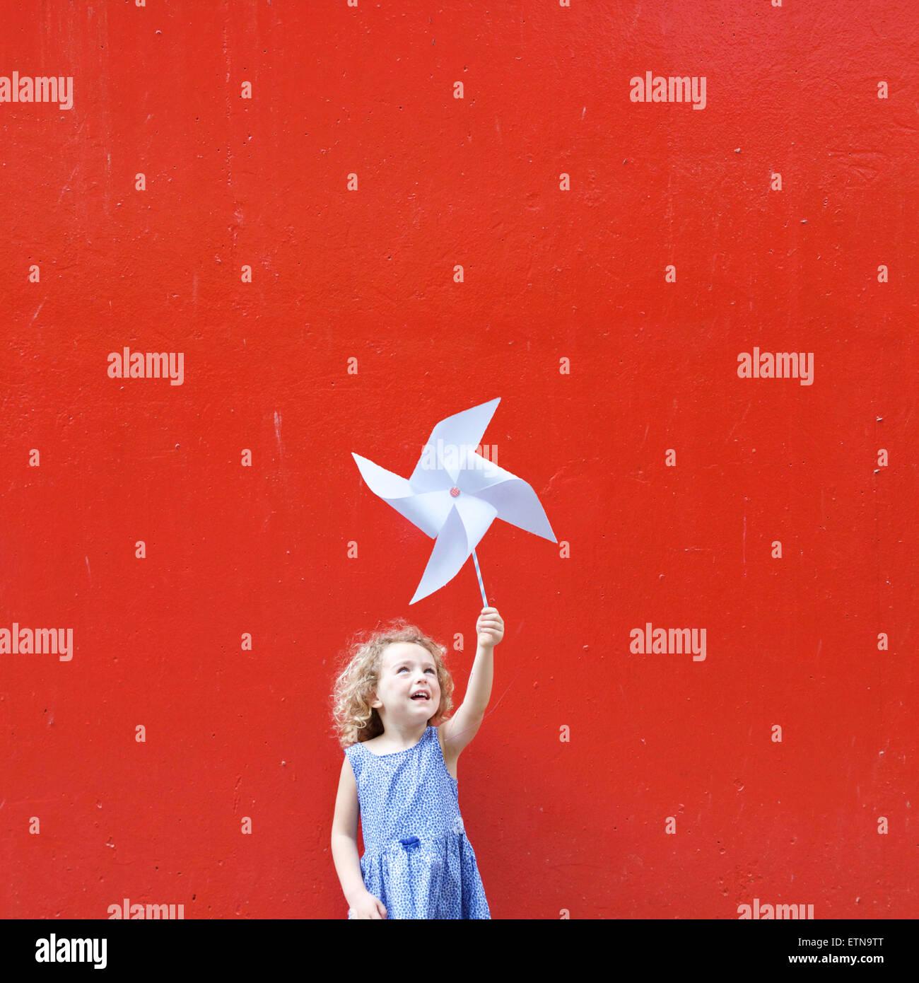 Lächelndes Mädchen hält ein Windrad in der Luft, so dass eine Hong Kong-Flagge Stockbild