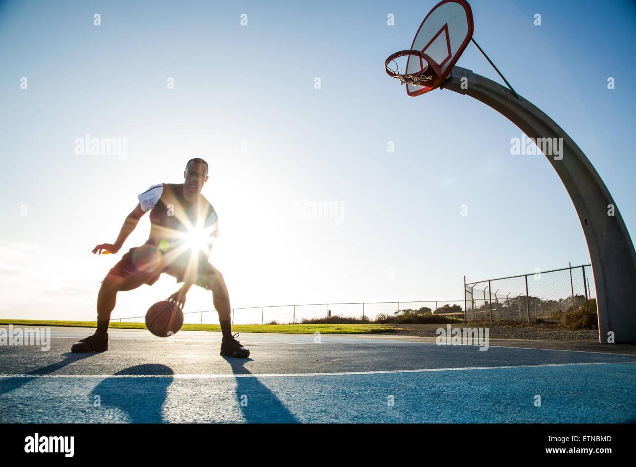 Junger Mann spielen Basketball in einem Park, Los Angeles, Kalifornien, USA Stockbild