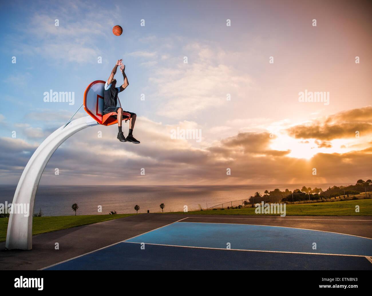 Junger Mann sitzt in einem Basketballkorb in einem Park, Los Angeles, Kalifornien, USA Stockbild