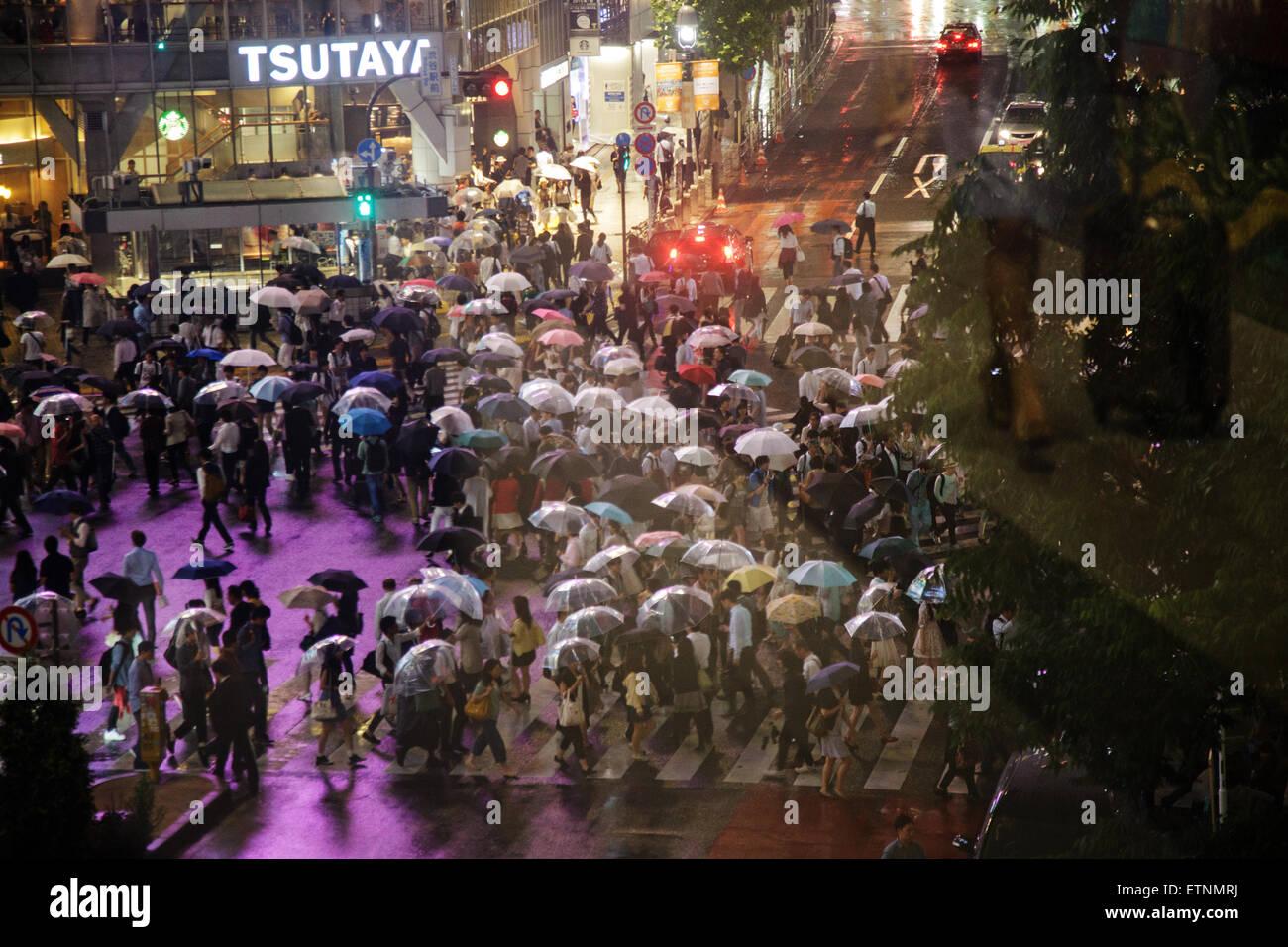 Menschen Sie mit Regenschirmen in einer regnerischen Nacht, überqueren die Straße Kreuzung genannt Kreuzung Stockbild