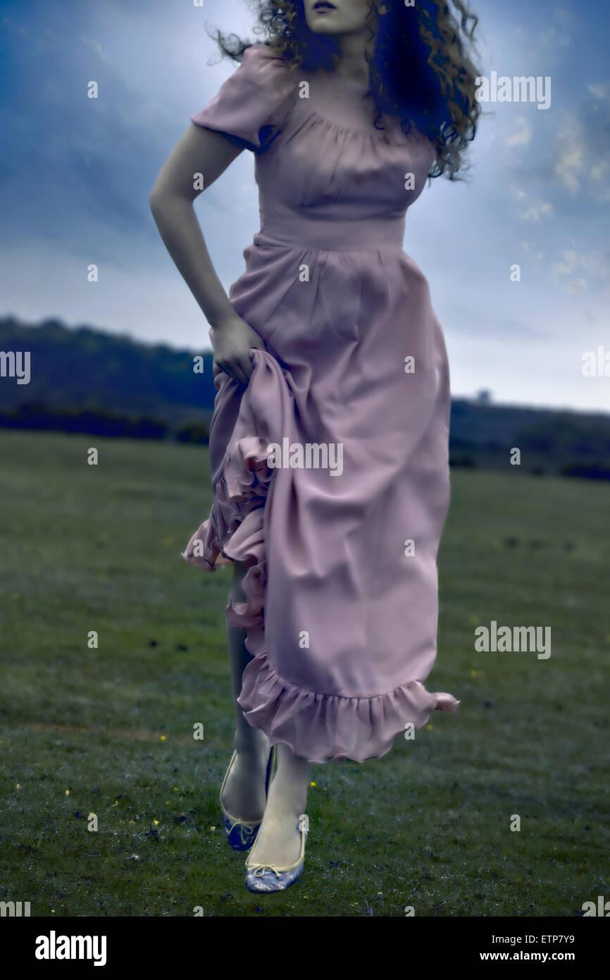 eine Frau in einem rosa Kleid läuft auf einer Wiese Stockbild