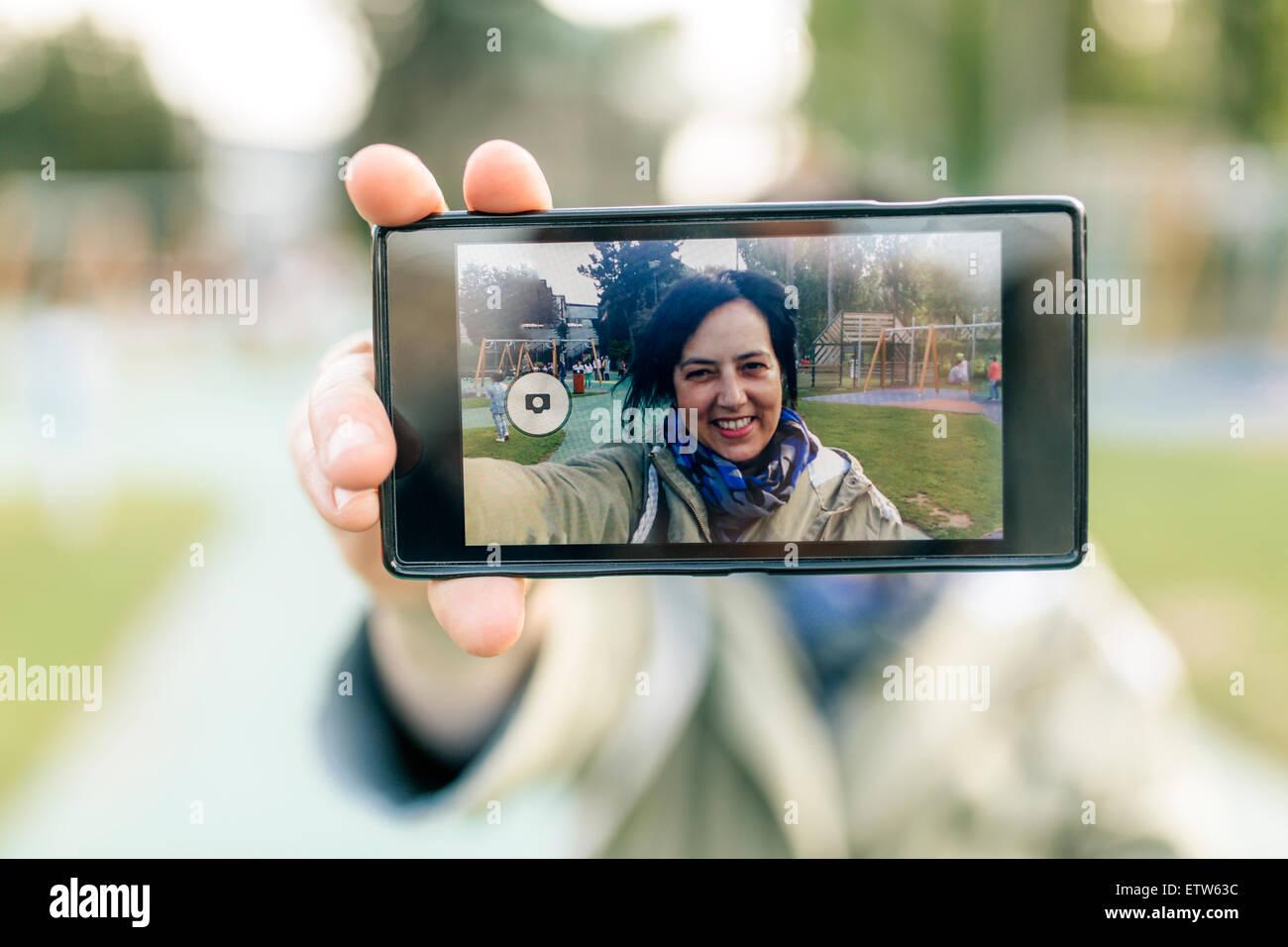 Reife Frau unter Selfie, mit Smartphone Stockbild