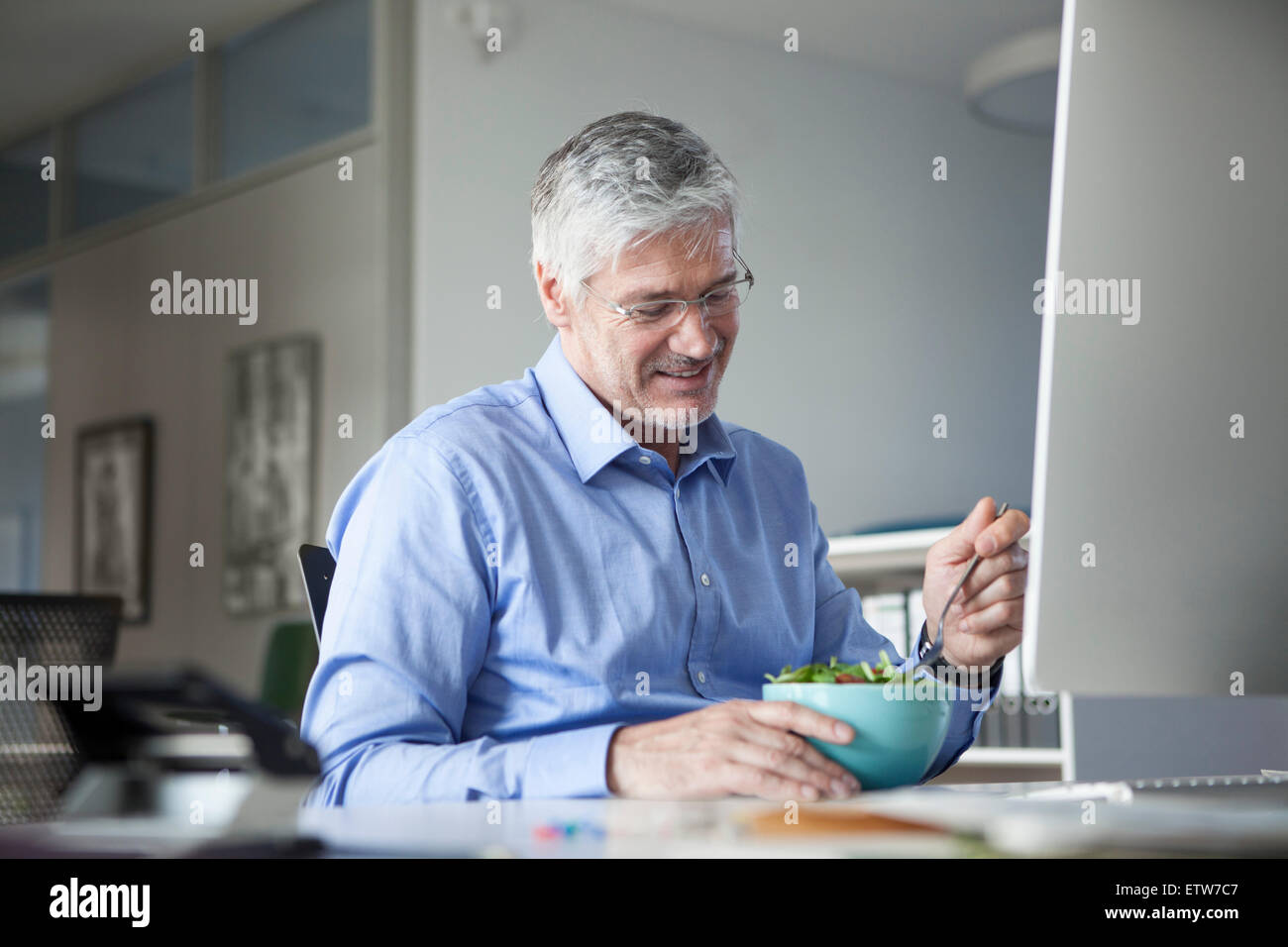 Geschäftsmann am Schreibtisch, Salat essen Stockbild