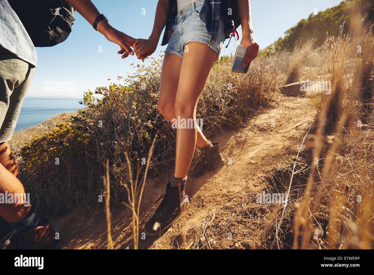 Nahaufnahme des jungen Paares auf einer Wanderung. Bild der junge Mann und Frau Wanderer, Hand in Hand während Stockbild