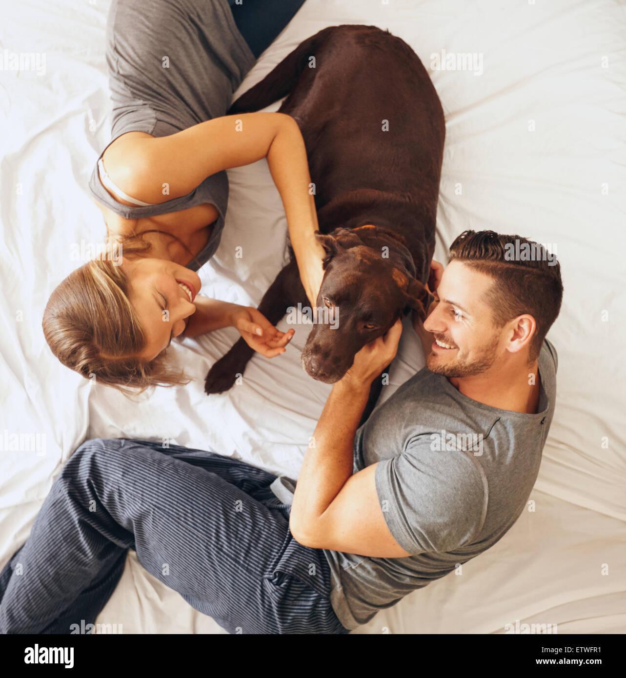 Draufsicht der glückliche junge Familie gemeinsam auf Bett entspannen. Mann und Frau mit Hund im Schlafzimmer. Stockbild
