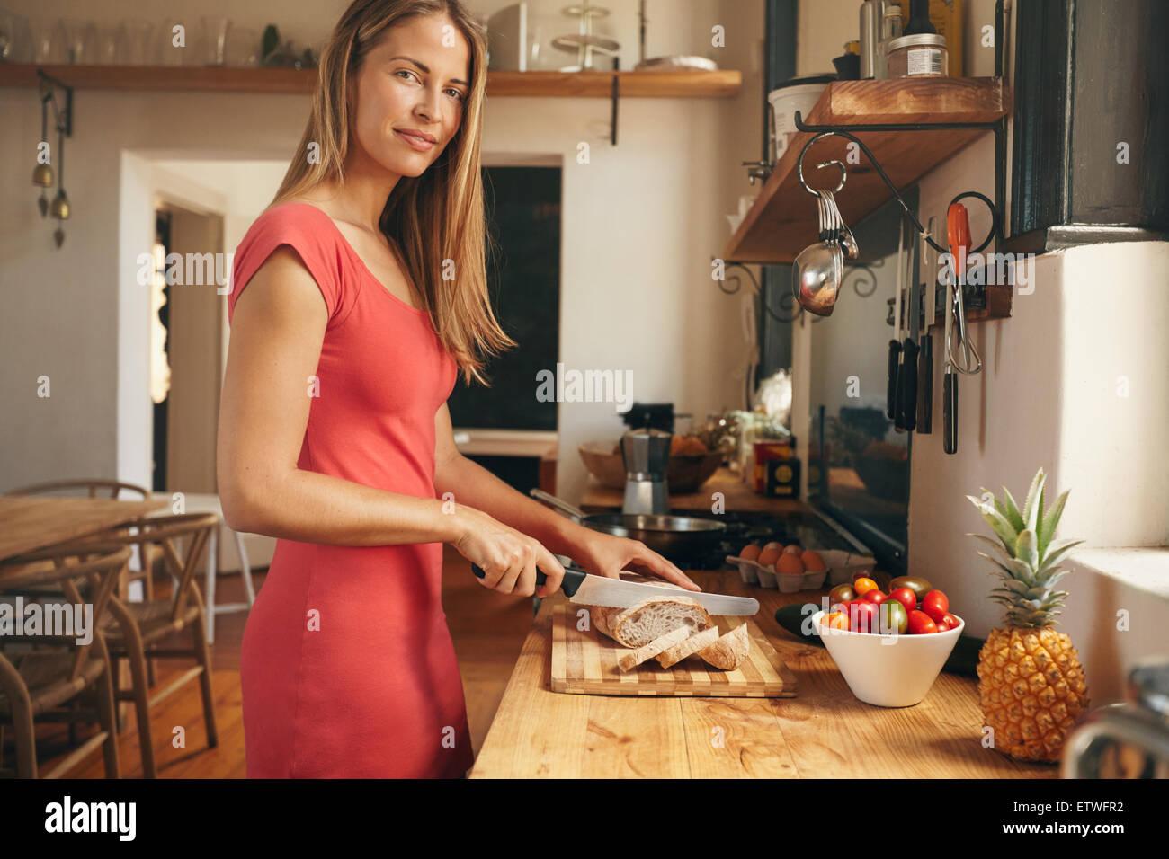 Schöne junge Frau schneidet ein frisch gebackenes Brot in der heimischen Küche. Kaukasische Frau Blick Stockbild
