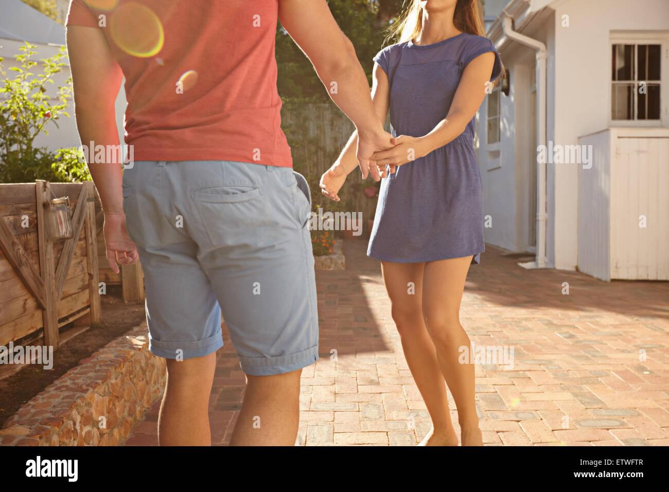 Aufnahme des jungen Paares stehen vor ihrem Haus Hand in Hand abgeschnitten. Mann und Frau in Casuals außerhalb Stockfoto