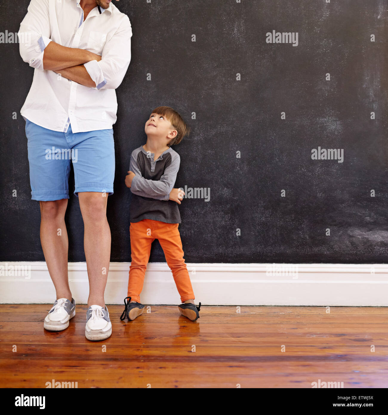 Innenaufnahme von kleinen Jungen und seinem Vater mit Hände gefaltet gegen schwarze Wand stehend. Vater und Stockbild