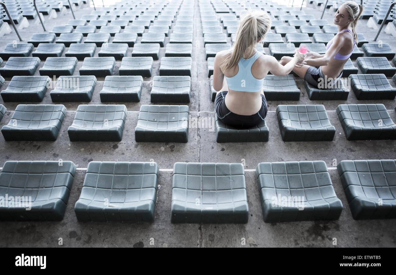 Zwei Sportler sitzen auf der Tribüne eines Stadions Stockbild