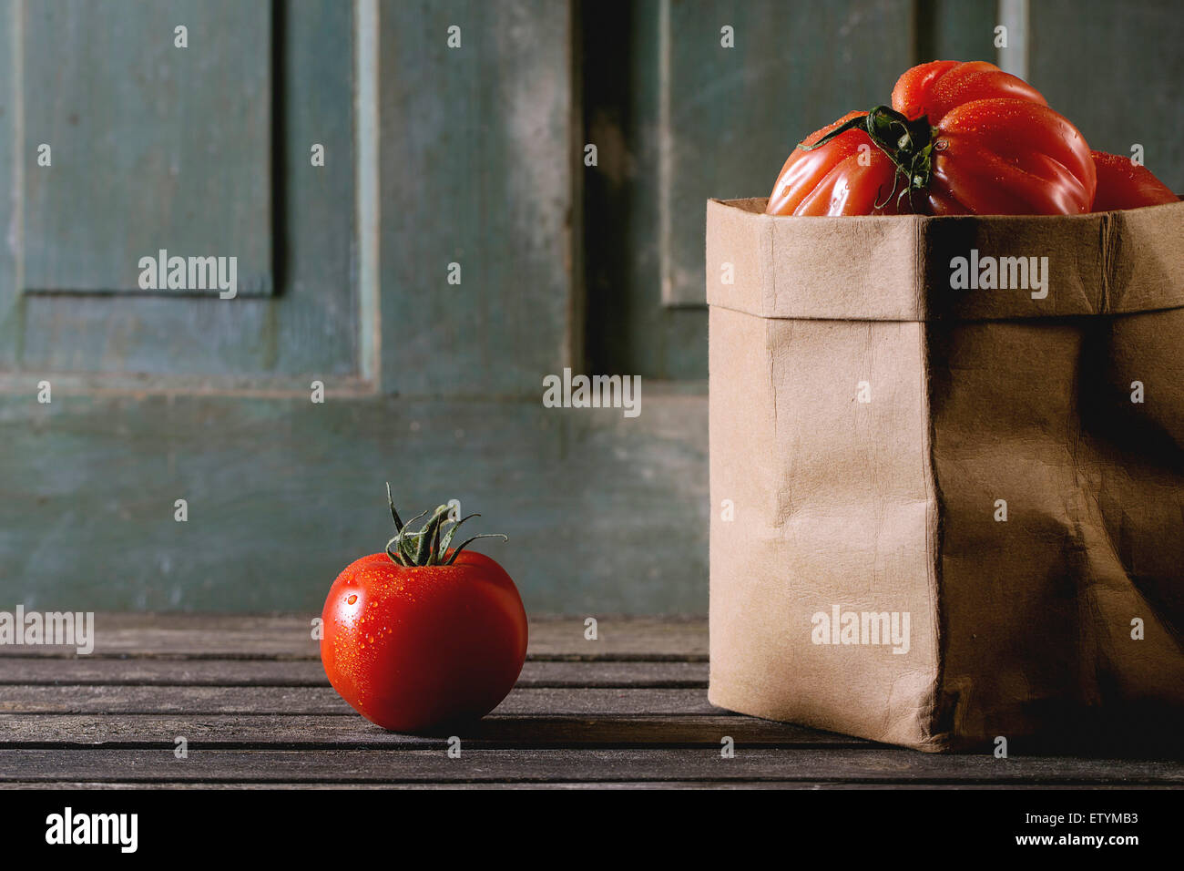 Eins und Haufen von großen roten Tomaten RAF in Papiertüte über alten Holztisch. Dunkle, rustikale Stockbild