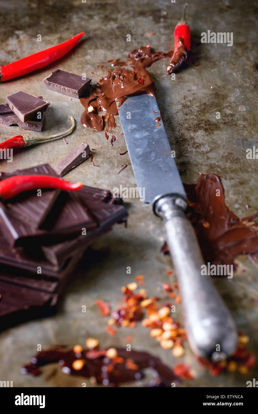 Hacken und schmelzen dunklen Schokolade mit frischen und trockenen roten hot Chili Peppers und Vintage Messer über Stockbild