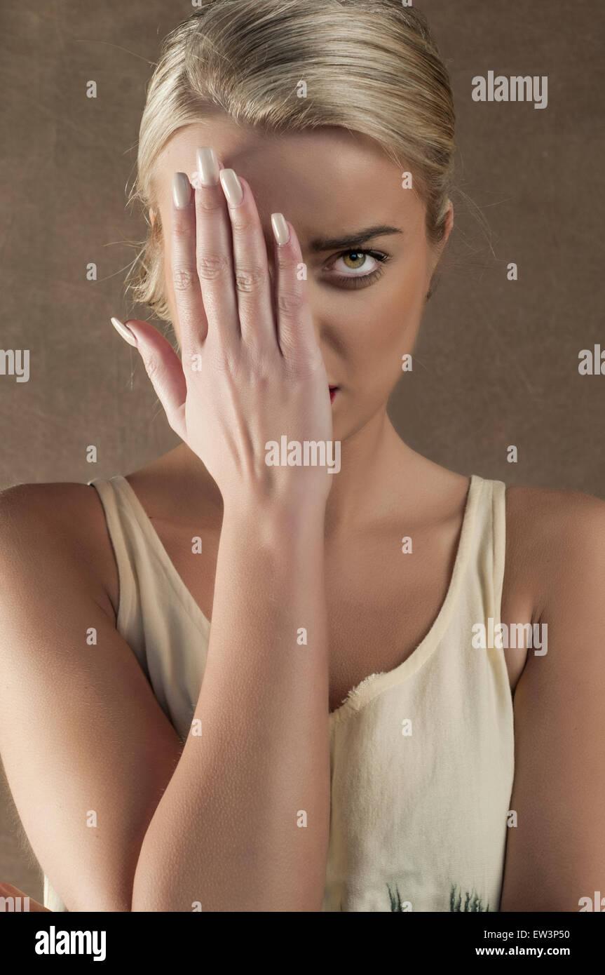 Junge Frau Gesicht mit der Hand versteckt Stockbild