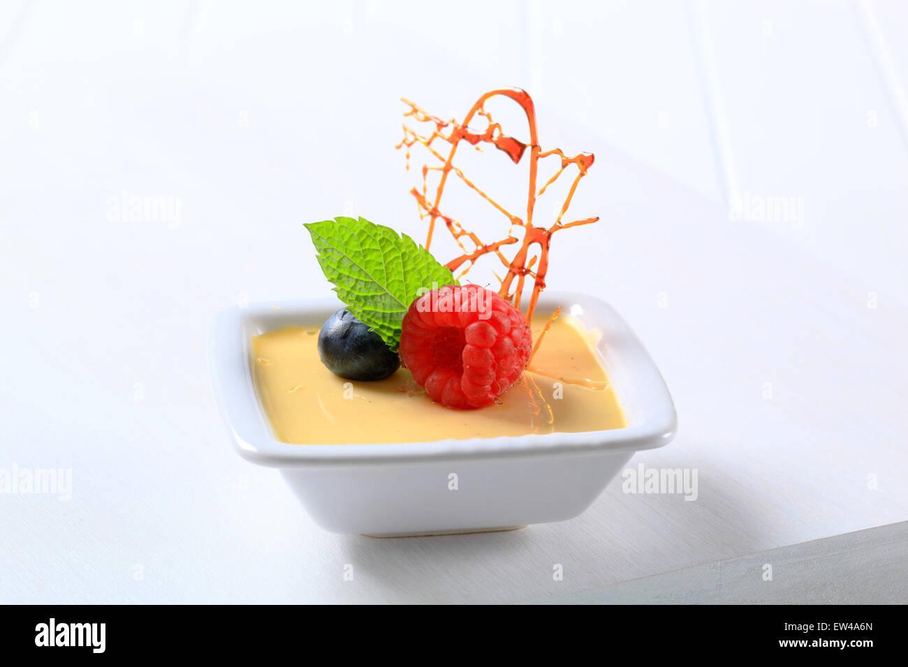 Kleine Schüssel mit Vanille Pudding mit Früchten garniert Stockbild