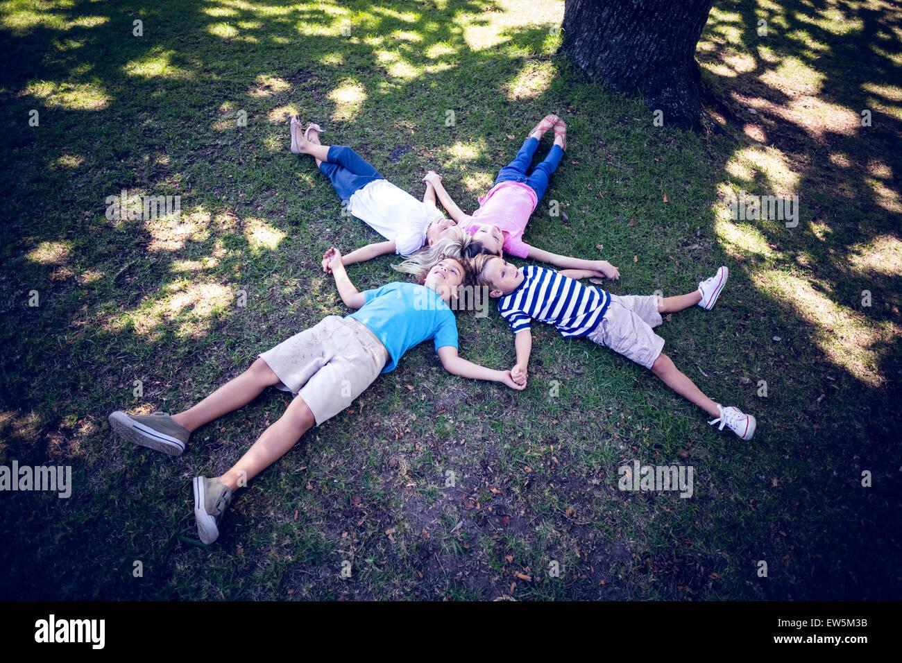 Glückliche Familie im Park liegend Stockbild