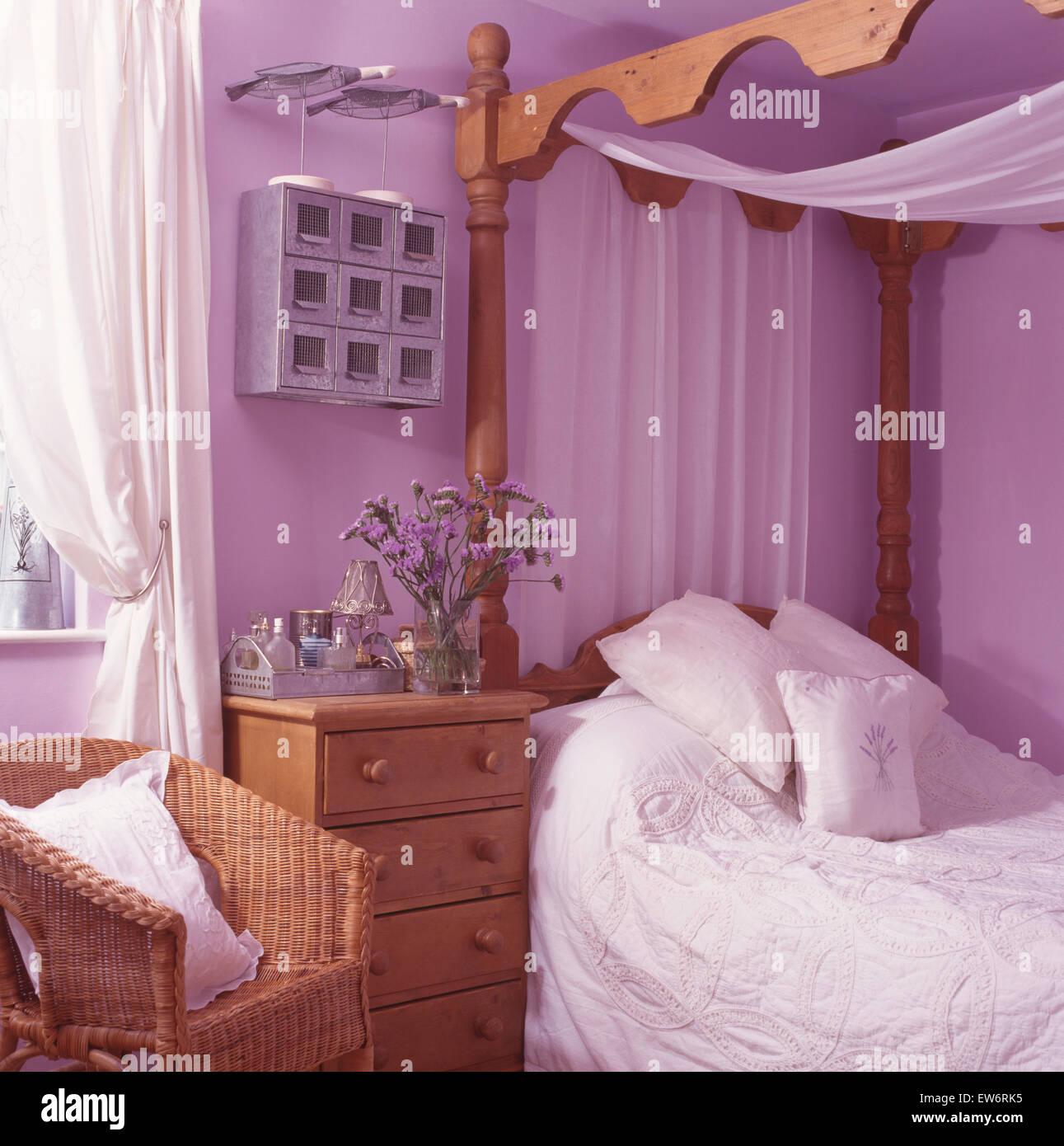 weien voile vorhnge auf kiefer vier himmelbett in einer lila neunziger jahre schlafzimmer mit korbstuhl stockbild - Gotische Himmelbettvorhnge