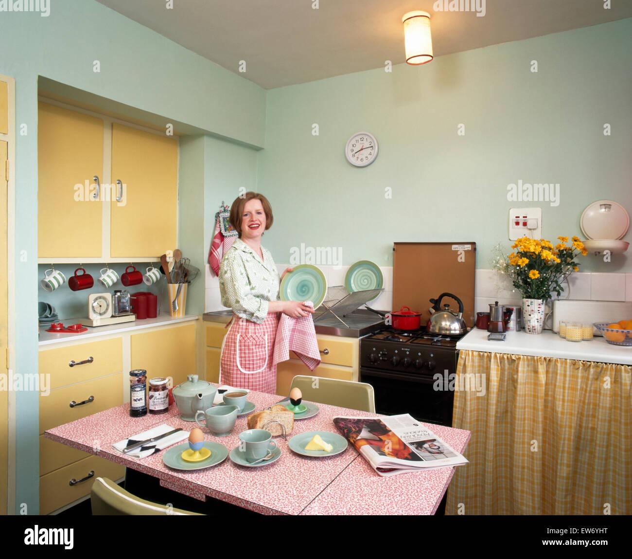 Porträt einer jungen Frau, die Trocknung Gerichte in neunziger Jahre, Wirtschaft Küche für nur zur Stockbild