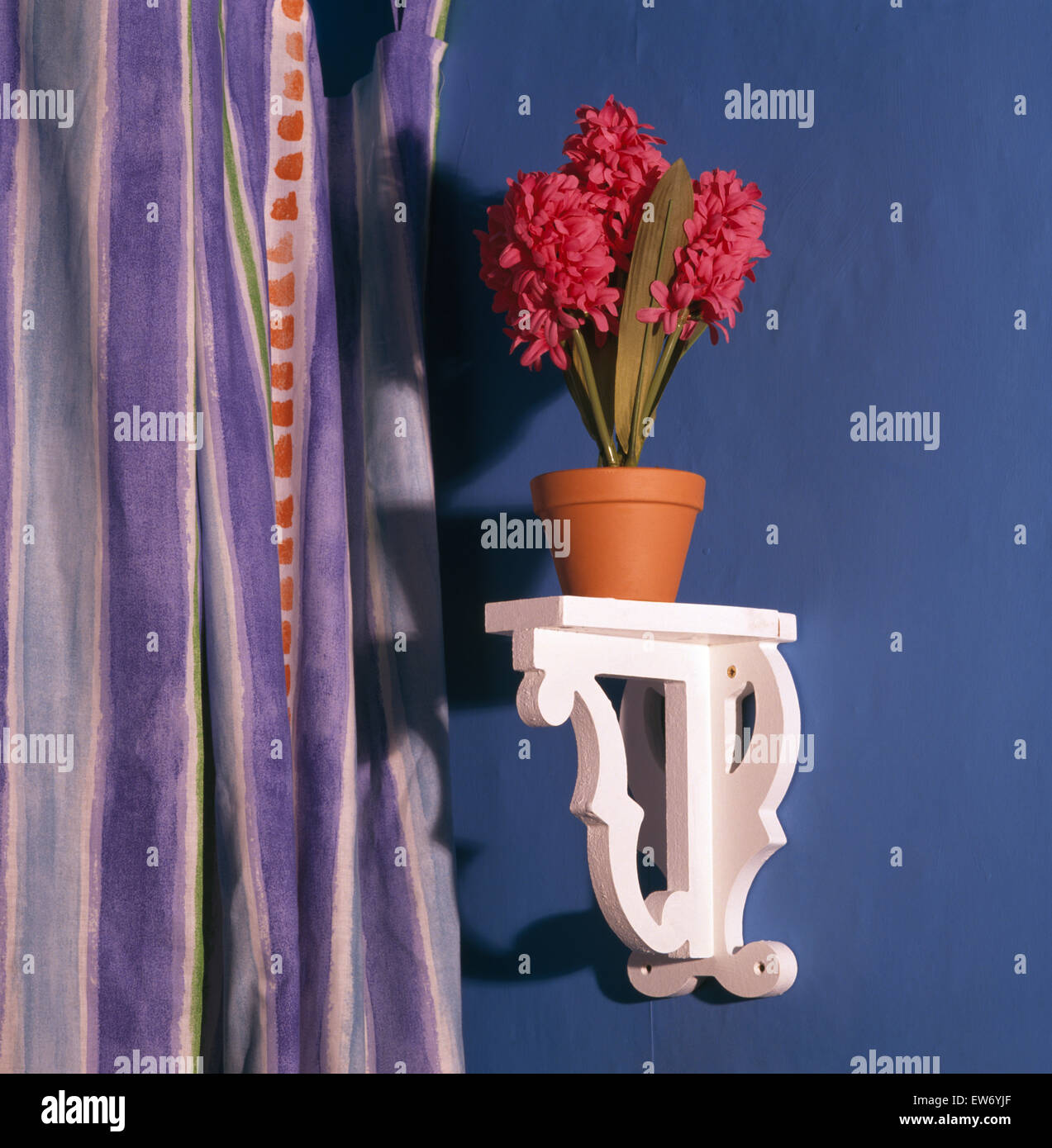 Nahaufnahme eines Topfes des künstlichen Hyazinthen auf einem kleinen weißen Holzregal Stockbild