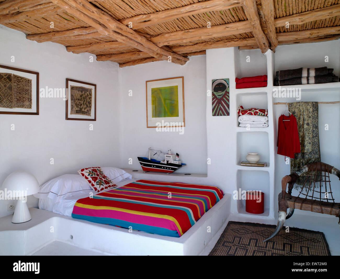 Schlafzimmer Bunt weißen kissen und bunt gestreiften bettdecke auf steinernen