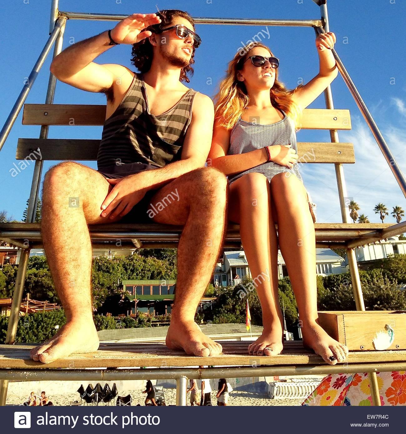 Mann und Frau sitzen auf einem Rettungsschwimmer-Turm, Clifton Beach, Cape Town, Südafrika Stockbild