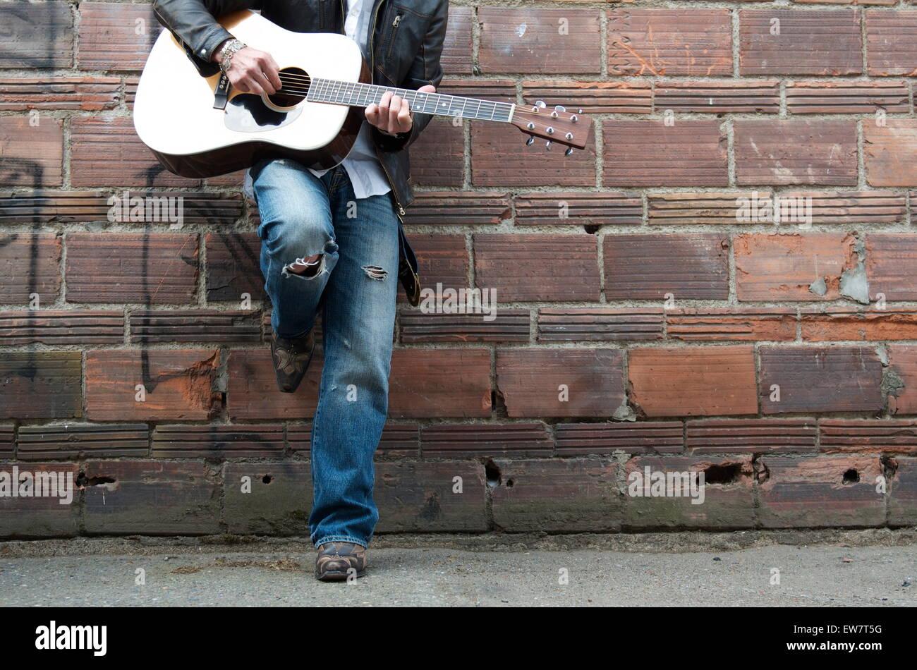 Mann in Lederjacke und Cowboy-Stiefel, die Gitarre zu spielen, in einer Gasse Stockbild