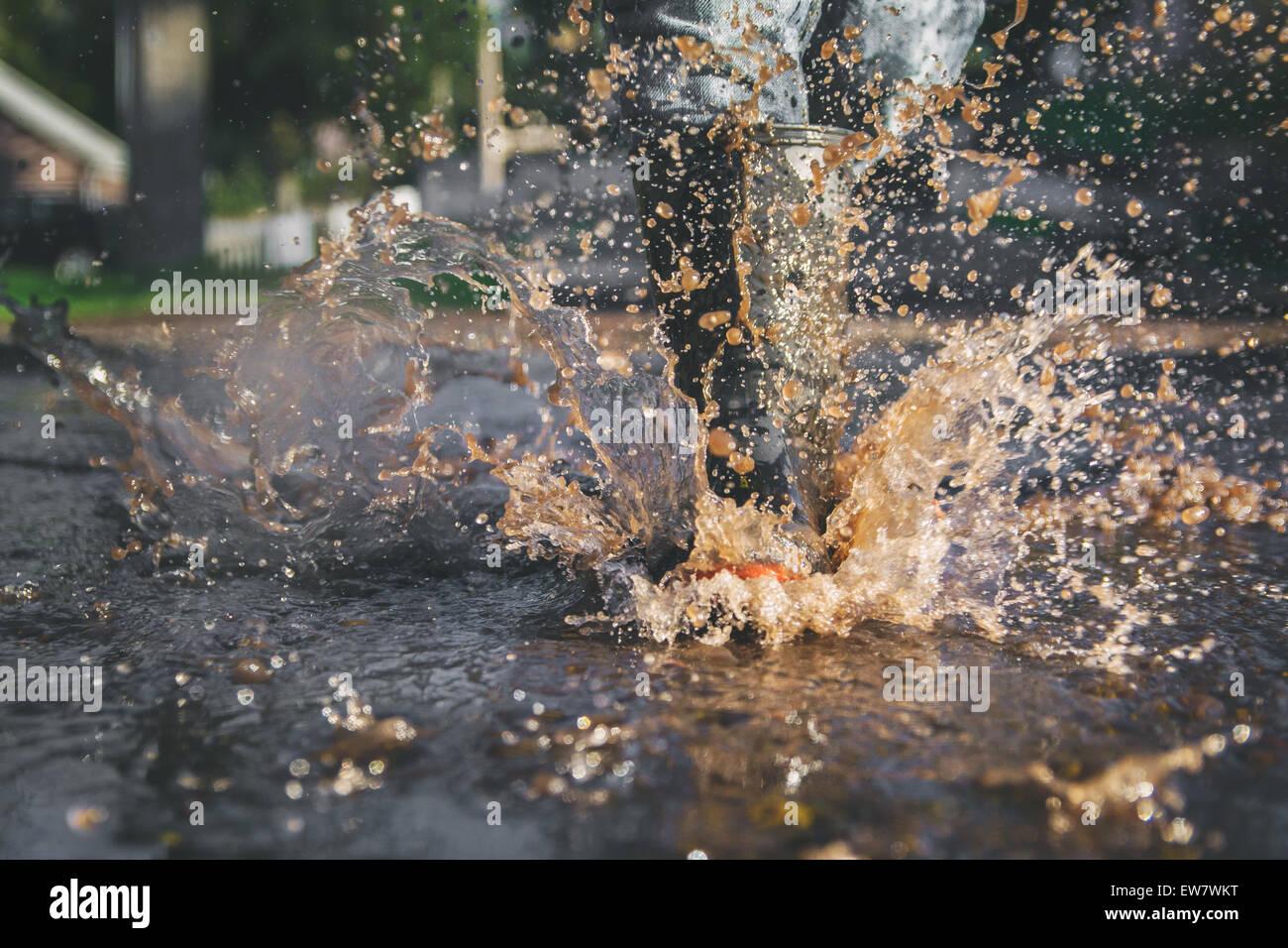 Die Beine des Kindes in einer Pfütze Wasser spritzt in Nahaufnahme Stockbild