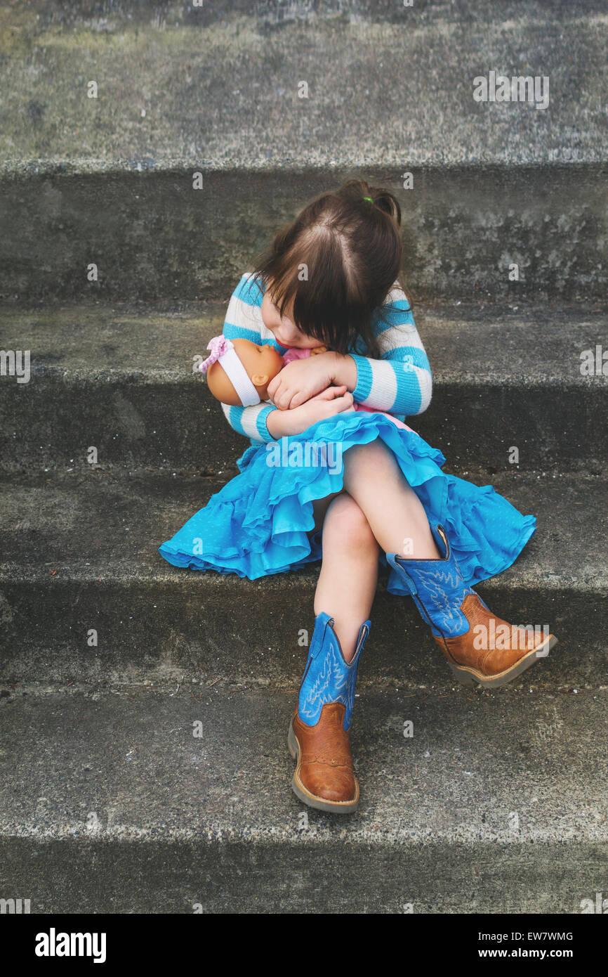 Mädchen sitzen auf einem Schritt umarmt eine Babypuppe Stockfoto