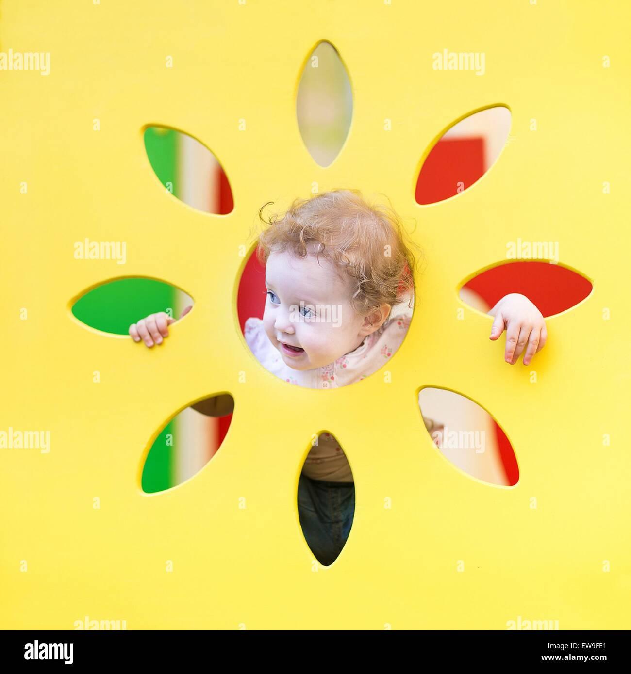 Lustige lockiges Babymädchen spielen verstecken und suchen Stockbild